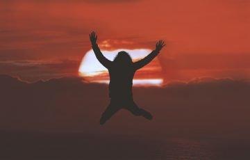 太陽とジャンプしている人