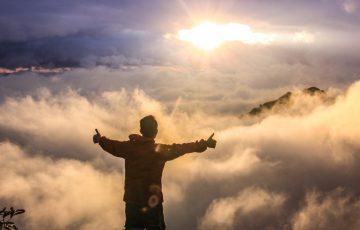 山の上で雲の上の朝日を見ている