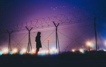 夜、フェンス越しに立つ人