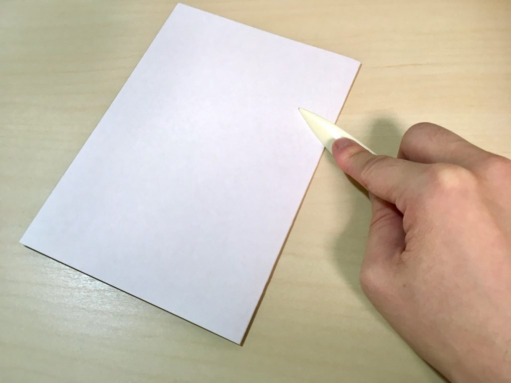 ヘラを使用して、厚紙を折っているところ