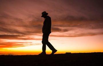 夕陽の空を背景に歩く人