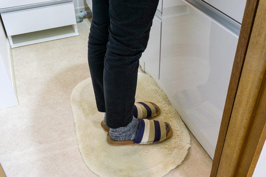 腰痛の際に、洗面台の前で両足をそろえて立つ