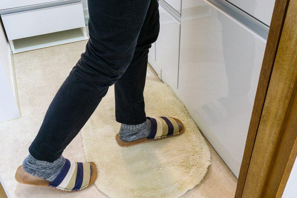 腰痛の際に、洗面台の前で片足を引いて腰を曲げる