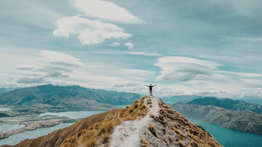 山の上に建つ男性と眼下に広がる湖と山