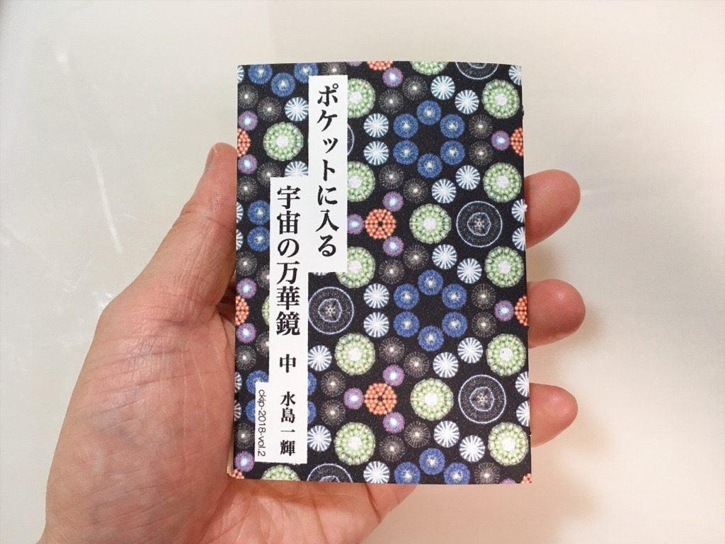 新作一文物語手製本「ポケットに入る宇宙の万華鏡 中」を手に持っているところ