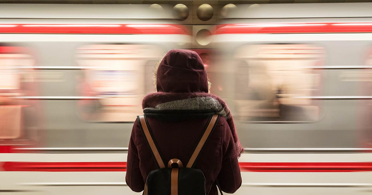 通り過ぎる列車の前に立つ女性