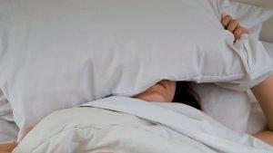 枕を押さえて寝込んでいる