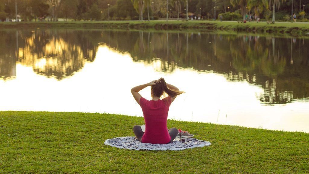 湖畔に座っている女性の後ろ姿
