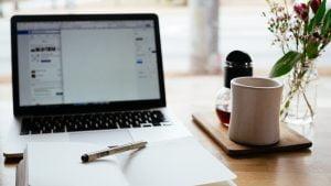 Macbookとメモ帳とカップ